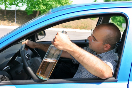 drinking drunk: Drunk man sitting in drivers and holding a bottle alcohol Stock Photo