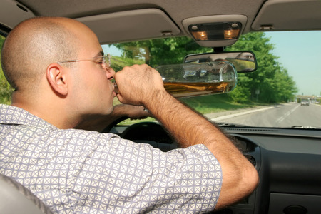 imprison: Drunk man sitting in drivers sit and drinking from a bottle