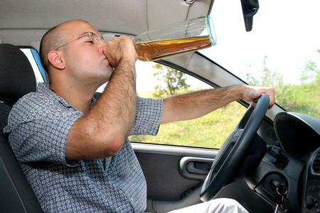 Drunk man sitting in drivers sit and drinking from a bottle photo