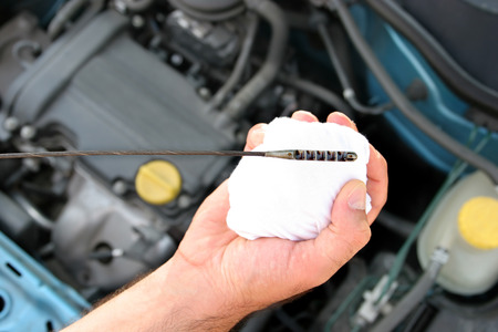 oil change: Details checking engine oil dipstick in car Stock Photo