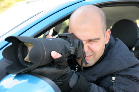 Professional photographer in action with telephoto lens, paparazzi