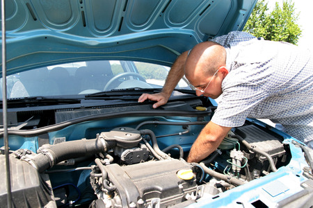 Businessman opening the trunk and checking the engine of a car Stock Photo