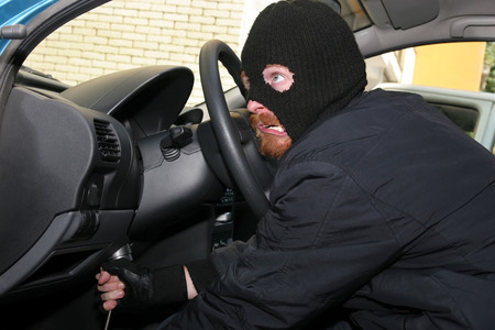 stealer: burglar wearing a mask (balaclava), details car burglary inside Stock Photo