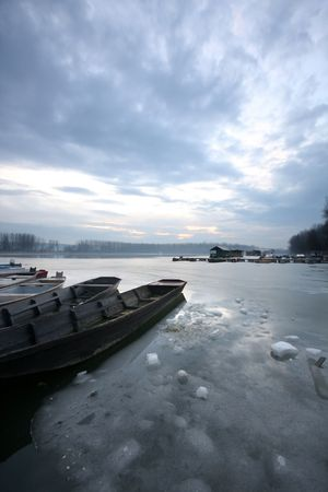 old boat on frozen river Danube in january photo