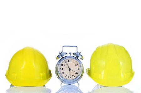 alarm clock and helmet on white background photo