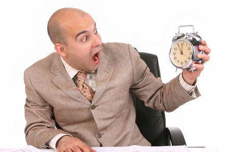 businessman looking at clock alarm at a desk photo