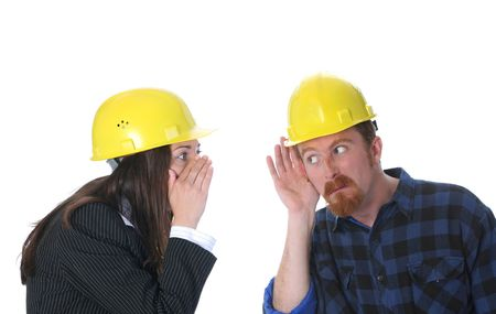 discretion: businesswoman gestures telling something to construction worker on workplace Stock Photo