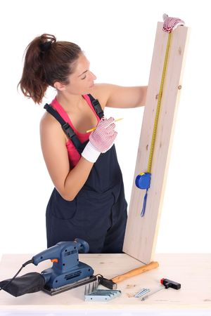 servicewoman: woman carpenter with wooden plank and measuring tape