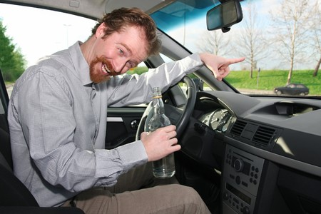 drinking and driving: Drunk man sitting in drivers with a bottle alcohol Stock Photo