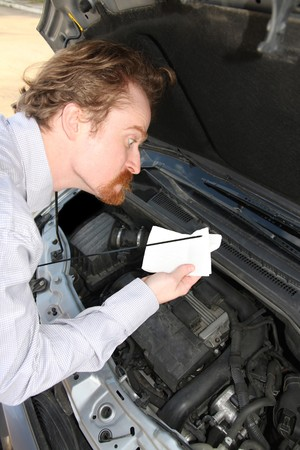 Funny man checking engine oil dipstick in car photo