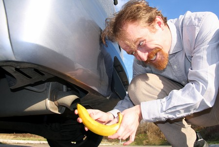bannana: Man putting banana into car exhaust pipe