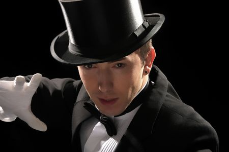 young magician with high hat on black background Stock Photo