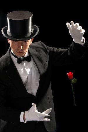 mago: joven mago de la realizaci�n de rosa roja sobre fondo negro Foto de archivo