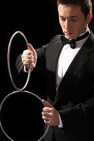 show ring: young magician with silver metal rings on black background