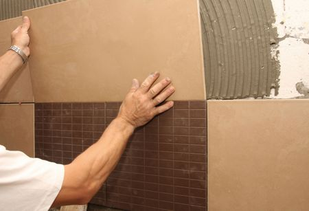 details of laying ceramic tile on wall Stock Photo