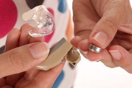 details hearing aid and battery in closeup