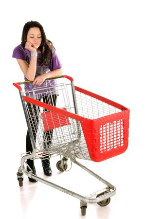 pauper: Unhappy girl with shopping cart over white background Stock Photo