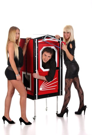 Magician performance and two beauty girls in a magic box with handsaw photo