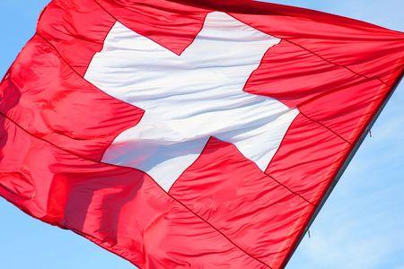 schweiz: wavy red and white Switzerland�flag over a blue sky