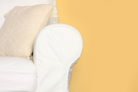 armrest: Details shot of a white couch near yellow wall
