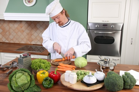 dinner wear: Young chef with vegetables, preparing lunch in kitchen