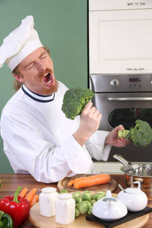 dinner wear: Funny young Chef with broccoli, preparing lunch in kitchen