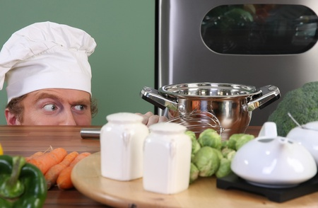 madman: Funny young chef strange looking at pot