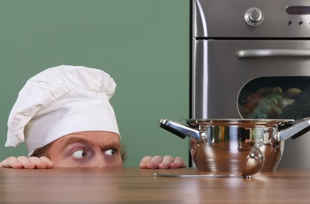 crazy people: Lustige junge Koch seltsamen Blick auf Topf