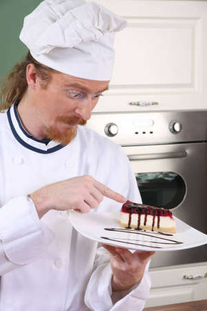 Funny young chef strange looking at piece of cake with chocolate sauce photo