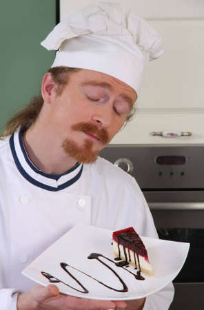 Funny young chef smelling a piece of cake with chocolate sauce photo