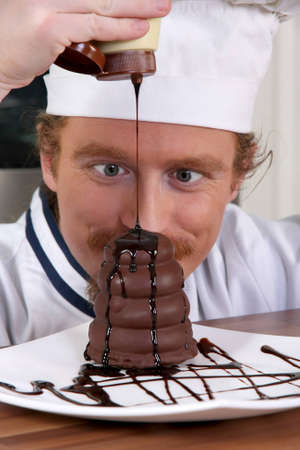 Funny young chef added chocolate sauce at piece of cake photo