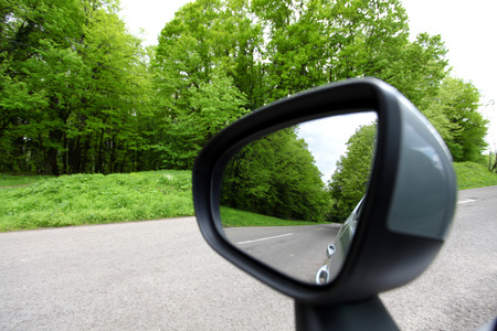 forest road reflection,  rearview car driving mirror view green forest road Stock Photo