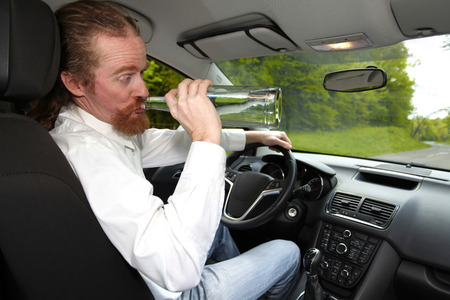 vodka bottle: Drunk man in car with a bottle alcohol