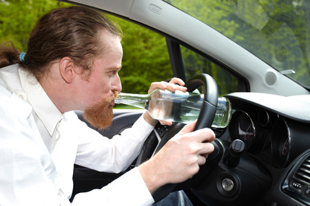 Drunk man in car with a bottle alcohol photo
