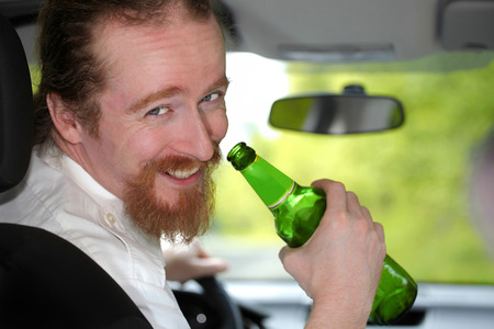 whiskey bottle: Drunk man in car with a bottle beer Stock Photo