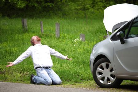 ドライバーの猛烈な道路で壊れた車 写真素材