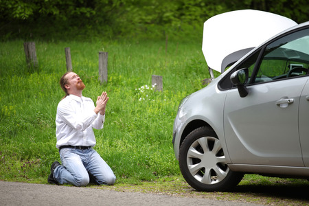 Funny driver praying a broken car by the road   Stock Photo
