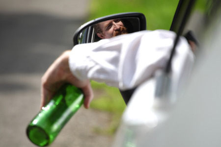 drinking and driving: Drunk man in car with a bottle alcohol