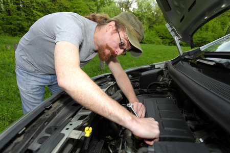 mechanic repairs a car on the road photo