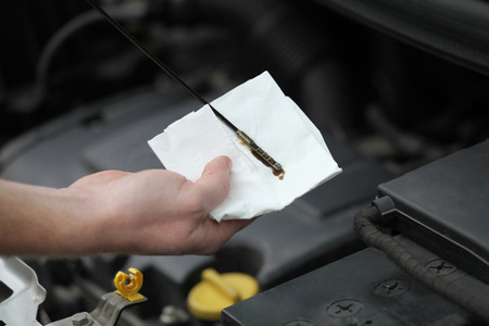 Auto mechanic checking engine oil dipstick in car. Auto mechanic in car repair