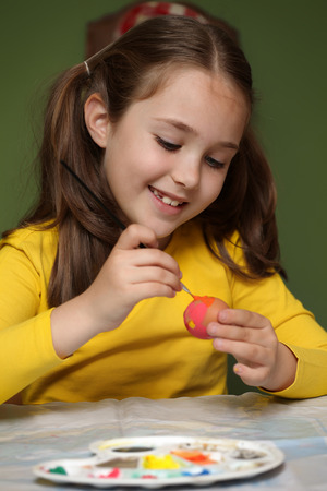 Girl painted Easter eggs at the table photo