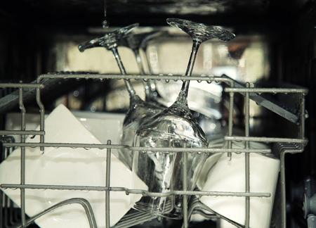 lavar platos: detalles del lavavajillas abierto, utensilios con gotas en durante el lavado Foto de archivo