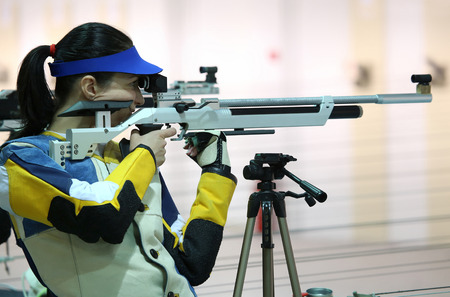 munition: Beautiful young woman aiming a pneumatic air rifle