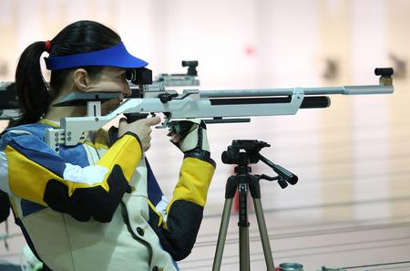 Belle jeune femme visant une carabine à air pneumatique Banque d'images - 39095974