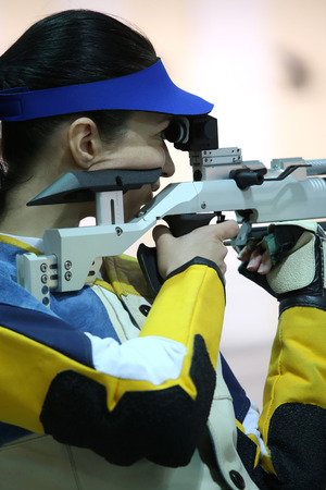 sniper training: beautiful young woman aiming a pneumatic air rifle