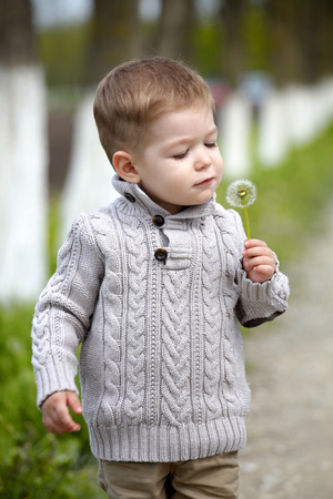fleece: 2 years old Baby boy with dandelion in spring park