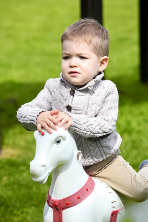 2 years: 2 years old Baby boy playing with horse on playground Stock Photo