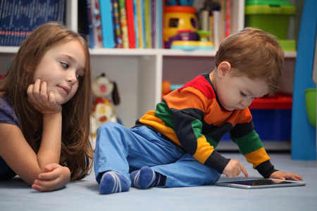 Disappointing girl with her little brother using a digital tablet computer photo