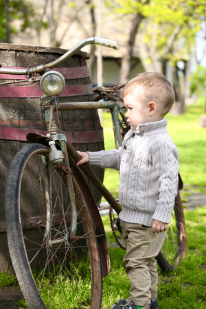 2 years old: 2 years old curious Baby boy walking around the old bike