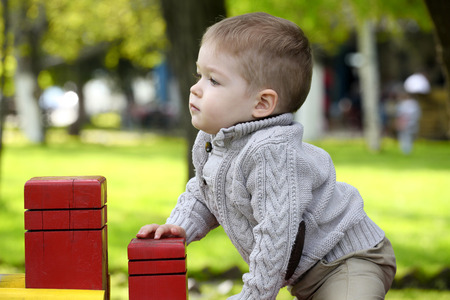 fleece: 2 years old Baby boy on playground in spring outdoor park Stock Photo
